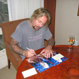 Photograph of Motley Crue's Vince Neil signing a Caricature I created and presented to him 